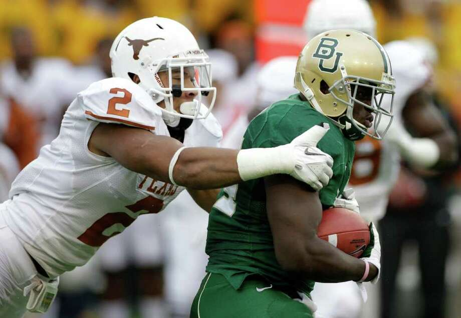 Texas cornerback A.J. White (2) attempts to bring down Baylor running back Terrance Ganaway (24) behind the line of scrimmage in the first half of an NCAA college football game Saturday, Dec. 3, 2011, in Waco. Photo: Tony Gutierrez, Associated Press
