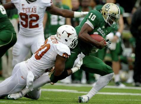 Texas defensive end Alex Okafor (80) brings down Baylor quarterback Robert Griffin III (10) following a short run in the first half of an NCAA college football game Saturday, Dec. 3, 2011, in Waco. Photo: Tony Gutierrez, Associated Press