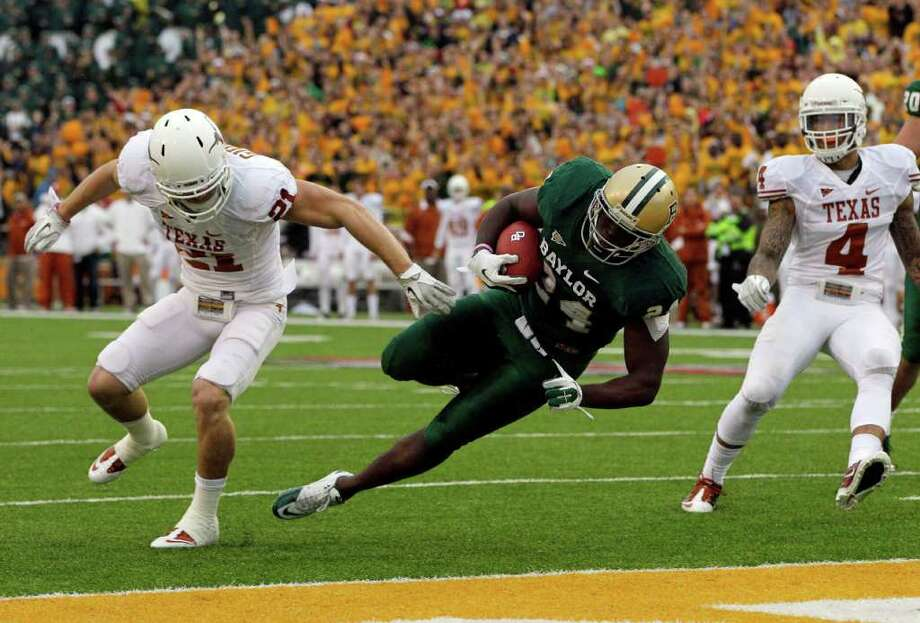 Texas' Kenny Vaccaro (4) looks on as safety Blake Gideon (21) hits Baylor running back Terrance Ganaway (24) as he Ganaway leaps into the end zone for a touchdown in the first  half of an NCAA college football game, Saturday, Dec. 3, 2011, in Waco. Photo: Tony Gutierrez, Associated Press