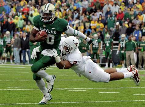 Baylor quarterback Robert Griffin III (10) attempts to escape a tackle by Texas cornerback A.J. White (2) in the first half of an NCAA college football game Saturday, Dec. 3, 2011, in Waco. Photo: Tony Gutierrez, Associated Press