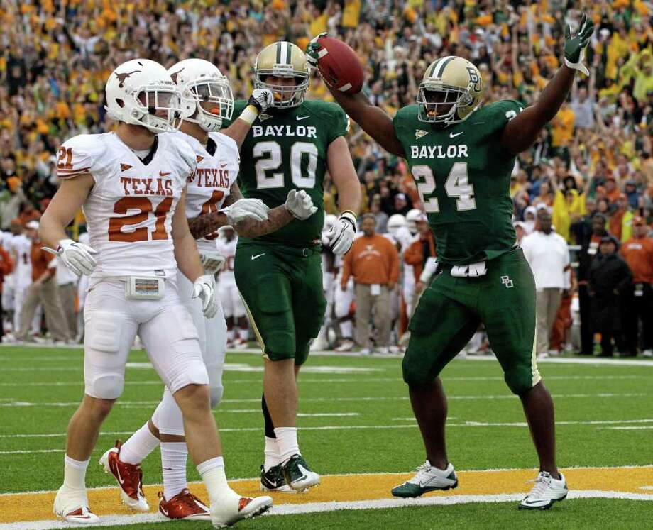 Baylor running back Terrance Ganaway (24) celebrates his touchdown with Jerod Monk (20) as Texas's Blake Gideon (21) and Kenny Vaccaro (4) look on in the first half of an NCAA college football game Saturday, Dec. 3, 2011, in Waco. Photo: Tony Gutierrez, Associated Press