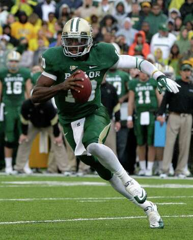 Baylor quarterback Robert Griffin III (10) finds running room behind the line of scrimmage against Texas in the first half of an NCAA college football game Saturday, Dec. 3, 2011, in Waco. Photo: Tony Gutierrez, Associated Press
