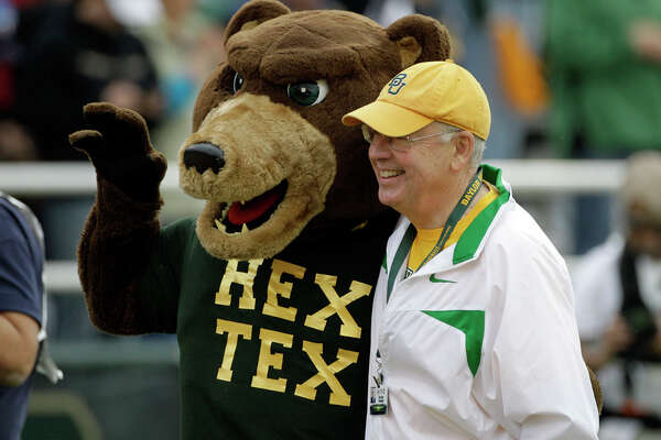 Baylor University president Ken Starr (right) poses with the university mascot before the start of an NCAA college football game against Texas, Saturday, Dec. 3, 2011, in Waco.