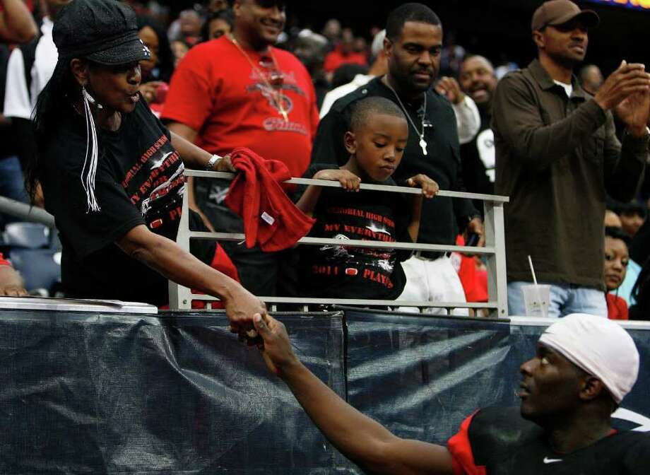 Port Arthur Memorial's quarterback Terrence Singleton is congratulated by his cousin Sandra Jones Forman after scoring a touchdown against La Porte during the third quarter of District 21-5A Regional Finals high school football playoff game at Reliant Stadium Saturday, Dec. 3, 2011, in Houston. Photo: James Nielsen, Houston Chronicle / © 2011 Houston Chronicle
