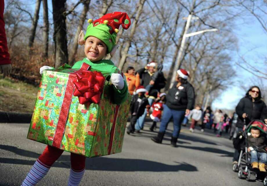 Five-year-old Leritbel Valle, of Bridgeport, is all wrapped up for the holidays as she marches to the PAL Christmas Village in Trumbull Saturday, Dec. 3, 2011 during a parade to kick off the season. Photo: Autumn Driscoll / Connecticut Post