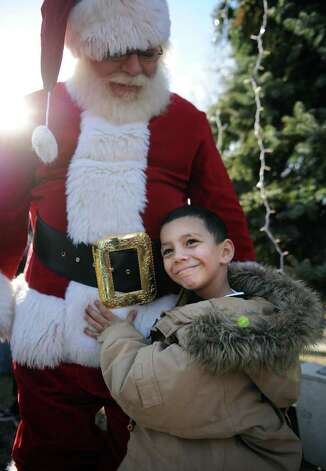 Five-year-old Tomas Nieves, of Bridgeport, poses with Santa following a parade to kick off the opening of the PAL Christmas Village Saturday, Dec. 3, 2011 in Trumbull, Conn. Photo: Autumn Driscoll / Connecticut Post