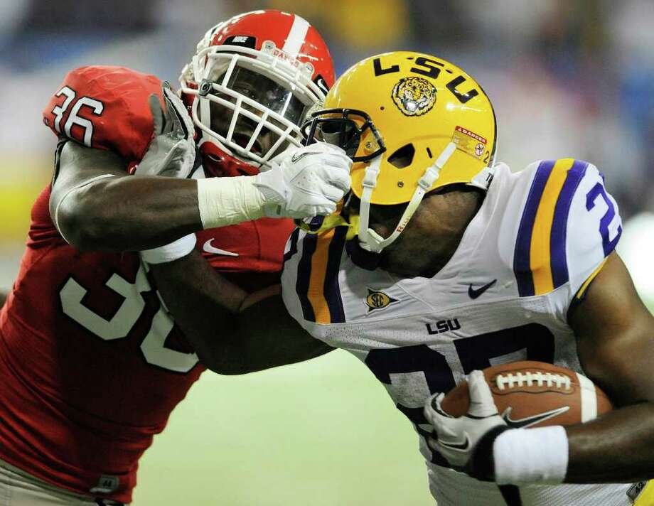 Georgia's Shawn Williams grabs LSU running back Kenny Hilliard's facemask as Hilliard scores one of his three touchdowns. Photo: AP