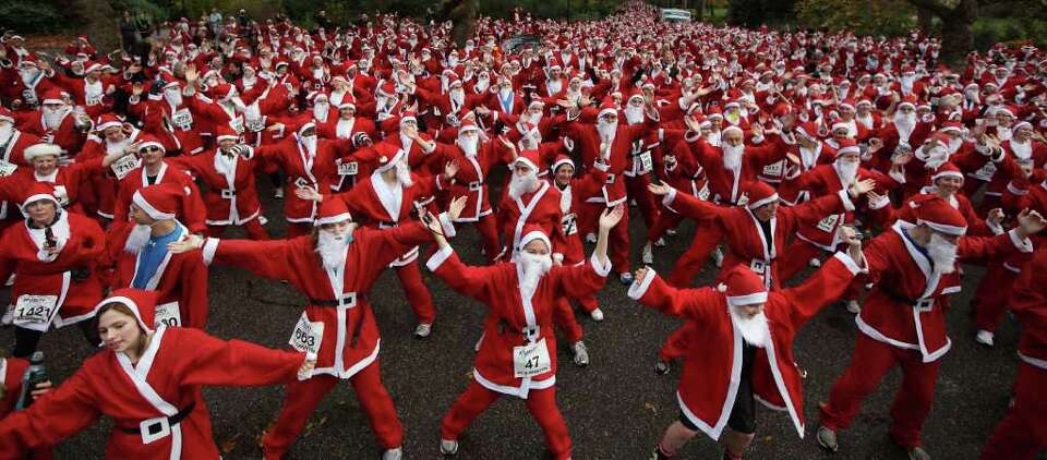 Charity runners dressed as Santa Claus warm up before taking part in the Disability Snowport UK fun