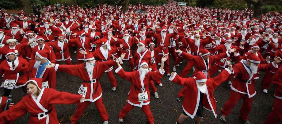 Charity runners dressed as Santa Claus warm up before taking part in the Disability Snowport UK fun run in Battersea Park on December 3, 2011 in London, England. 1600 runners took part in the 6 kilometer run to raise funds for the charity which helps disabled people take part in snow sports. Photo: Peter Macdiarmid, Getty / 2011 Getty Images