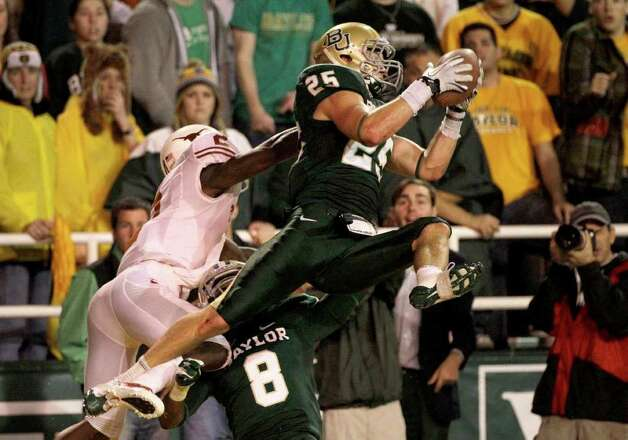 Baylor safety Sam Holl (25) intercepts a pass in the end zone intended for Texas' Marquise Goodwin (2) as Baylor' K.J. Morton (8) looks on in the second half of an NCAA college football game Saturday, Dec. 3, 2011, in Waco. The interception was Holl's second of the game in the 48-24 Baylor win. Photo: Tony Gutierrez, Associated Press