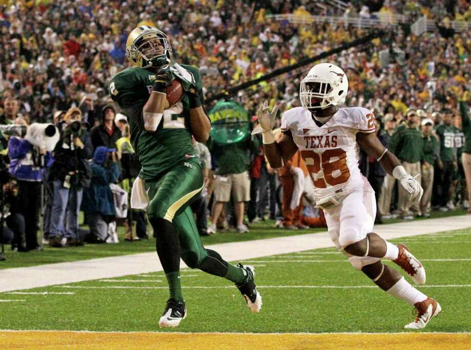 Baylor wide receiver Terrance Williams (2) comes down with a touchdown reception in front of Texas cornerback Quandre Diggs (28) in the second half of an NCAA college football game Saturday, Dec. 3, 2011, in Waco. Baylor won 48-24. Photo: Tony Gutierrez, Associated Press