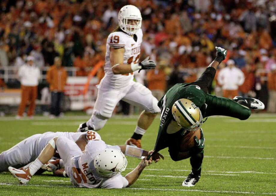 Texas quarterback Case McCoy, bottom left, drags down Baylor cornerback Ahmad Dixon (6) after Dixon picked up a fumble by Texas' Cody Johnson in the second half of an NCAA college football game Saturday, Dec. 3, 2011, in Waco. Baylor won 48-24. Photo: Tony Gutierrez, Associated Press
