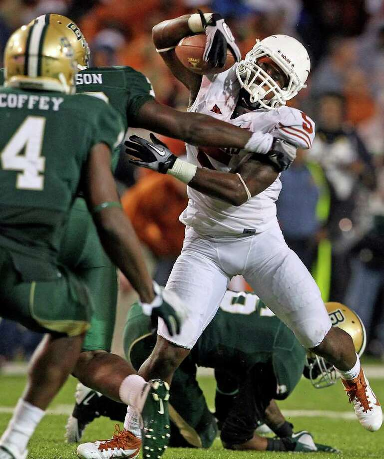 Longhorns running back Jeremy Hills struggles to keep possession in the fourth quarter as Baylor hosts Texas at Floyd Casey Stadium in Waco on  Saturday, Dec. 3, 2011. Photo: TOM REEL, SAN ANTONIO EXPRESS-NEWS  / © 2011 San Antonio Express-News