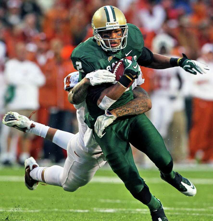 Bears wide receiver Terrance Williams swings Longhorn tackler Kenny Vaccaro after a catch as Baylor hosts Texas at Floyd Casey Stadium in Waco on Saturday, Dec. 3, 2011. Photo: TOM REEL, SAN ANTONIO EXPRESS-NEWS  / © 2011 San Antonio Express-News