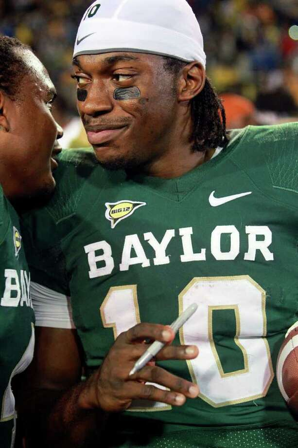 Robert Griffin III listens to a teammate as he signs autographs after Baylor's 48-24 win over Texas at Floyd Casey Stadium in Waco on  Saturday, Dec. 3, 2011. Photo: TOM REEL, SAN ANTONIO EXPRESS-NEWS  / © 2011 San Antonio Express-News