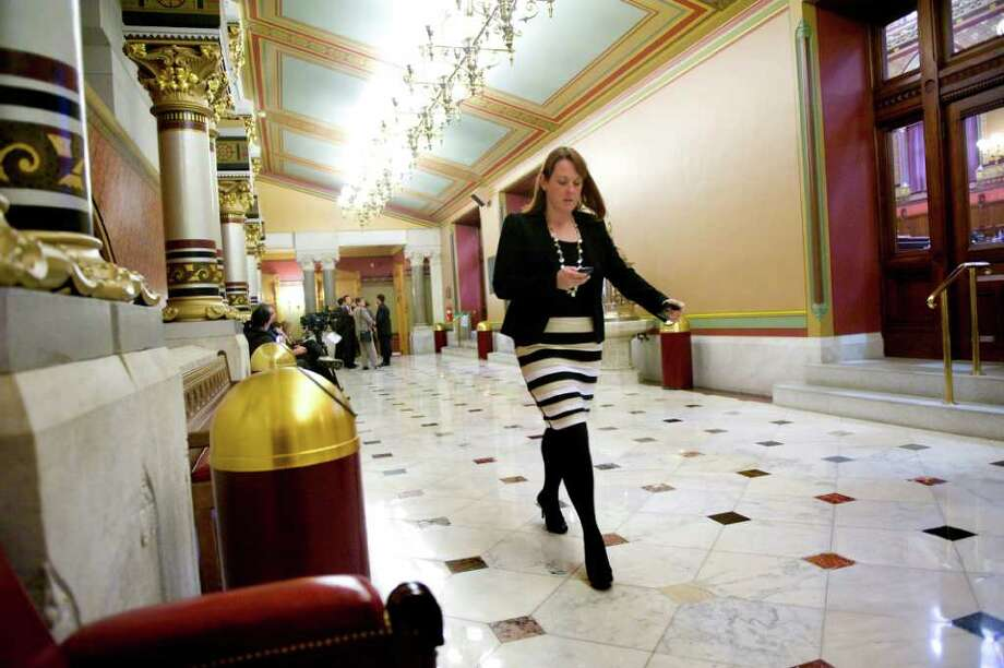 Spokeswoman Colleen Flanagan checks her messages as she rushes down the hallway at the state Capitol in Hartford, Conn., October 26, 2011. Photo: Keelin Daly / Stamford Advocate