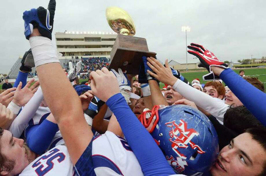 Members of the Midland Christian football hoist their TAPPS Division II State Championship trophy into the air after defeating Concordia Lutheran 35-23 Saturday at Leo Buckley Stadium, Killeen. Cindeka Nealy/Reporter-Telegram Photo: Cindeka Nealy, Midland Reporter-Telegram / Cindeka Nealy/Reporter-Telegram