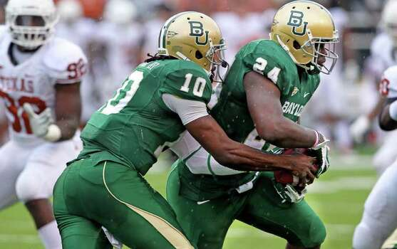 Bears running back Terrance Ganaway gets a handoff from Robert Griffin III in the rain as Baylor hosts Texas at Floyd Casey Stadium in Waco on Saturday, Dec. 3, 2011. Photo: TOM REEL, SAN ANTONIO EXPRESS-NEWS  / © 2011 San Antonio Express-News
