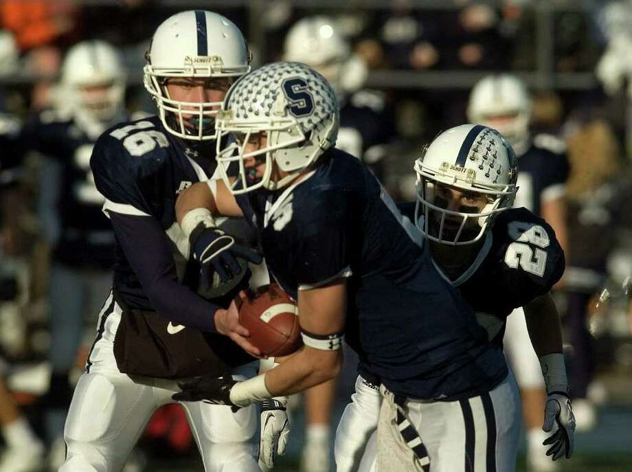 Staples quarterback Jack Massie hands the ball off to Nick Kelly during their class LL semifinal game against Newtown at Bunnell High School in Stratford on Saturday, Dec. 3, 2011. Staples won 44-20. Photo: Jason Rearick / The News-Times