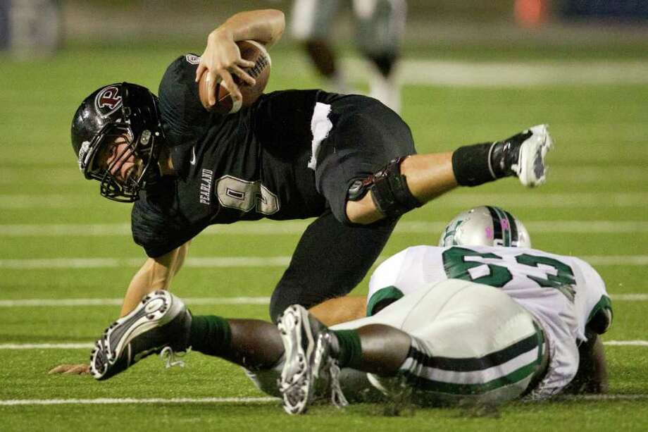 Pearland quarterback Jacob Garner (9) is upended by Hightower defensive lineman Derrick Smith (63) during the second half of the Class 5A Div. I Region III championship at Tully Stadium on Saturday, Dec. 3, 2011, in Houston. Photo: Smiley N. Pool, Houston Chronicle / © 2011  Houston Chronicle