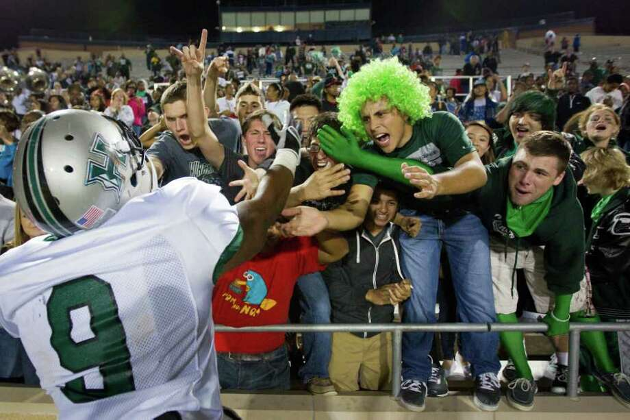 Hightower fans celebrate with linebacker  Myles Houston (9) after the Hurricanes defeated Pearland in the Class 5A Div. I Region III championship at Tully Stadium on Saturday, Dec. 3, 2011, in Houston. Photo: Smiley N. Pool, Houston Chronicle / © 2011  Houston Chronicle