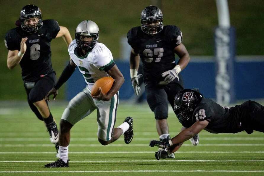 Hightower quarterback Bralon Addison eludes the Pearland defense of John Gibberman (6), Chris Alexan