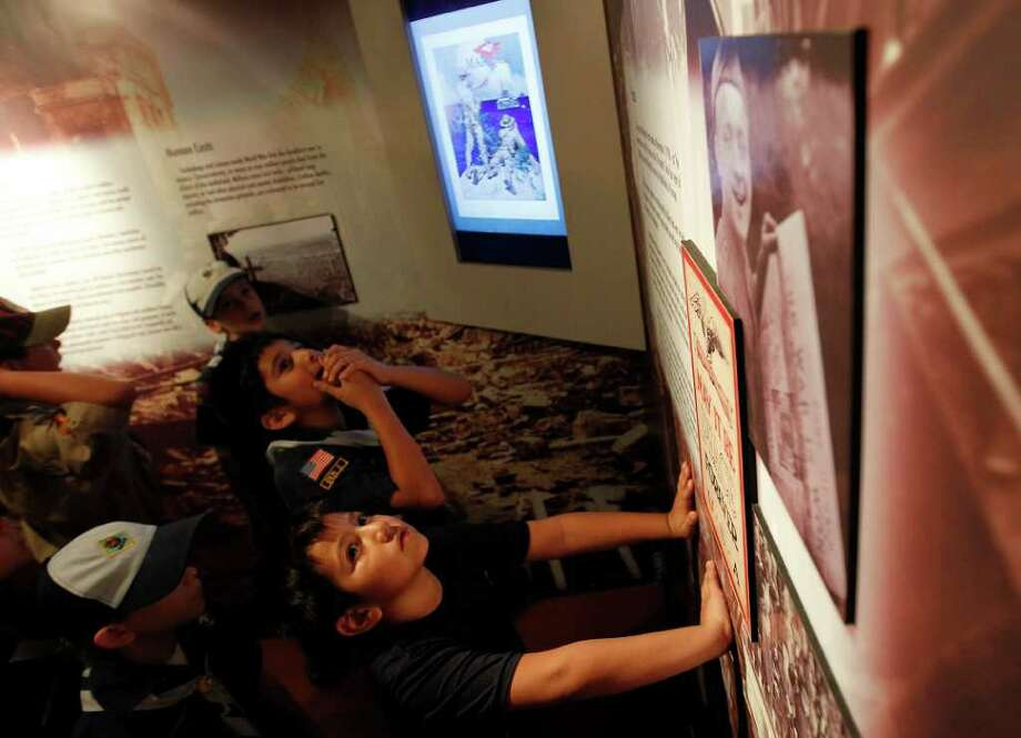Jose Sanchez, 6, foreground, with his brother, Ruben, 9, read the signs on the walls of the Waddell & Reed's ÒHonoring Our HistoryÓ Traveling World War I Exhibition, at the San Jacinto Monument, Dec. 3, 2011, as they and their fellow members of Pack 452, of Friendswood, take in the exhibit. Photo: Karen Warren, Houston Chronicle / © 2011 Houston Chronicle