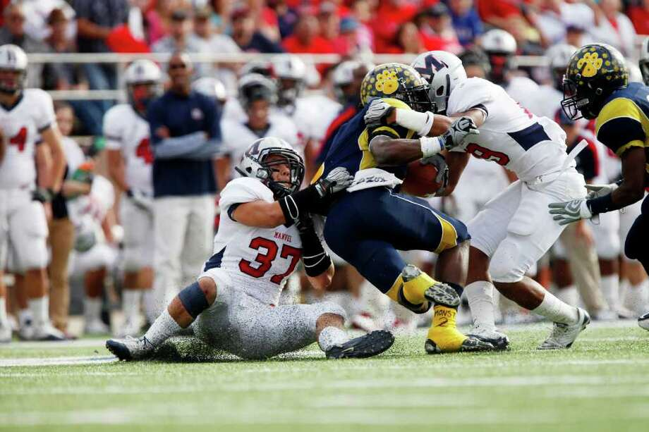 LaMarque running back Leonard Brooks (2) is pushed back by the Manvel defense during the first half of the Class 4A Division II Region III Championship between the La Marque High School Cougars and the Manvel High School Mavericks, Saturday, December 3, 2011 at Galena Park ISD Stadium in Houston, Texas. Manvel leads at the half, 31-14. Photo: TODD SPOTH, For The Chronicle / Todd Spoth