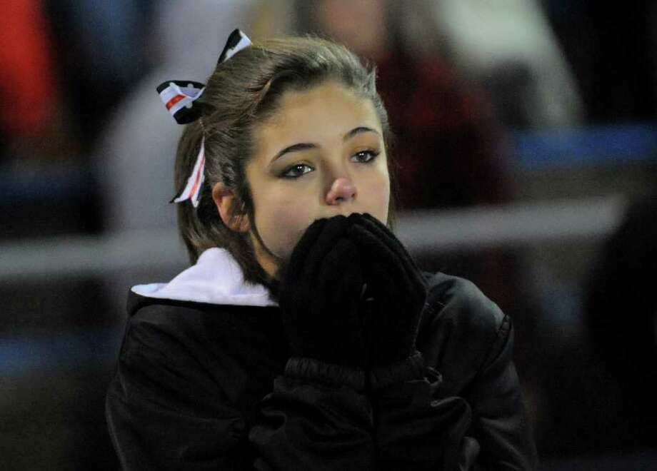 Masuk cheerleader Julia Hayes watches the final seconds of CIAC Class L boys football semifinal action against Daniel Hand in West Haven, Conn. on Saturday December 3, 2011. Hand defeated Masuk 35-14. Photo: Christian Abraham / Connecticut Post
