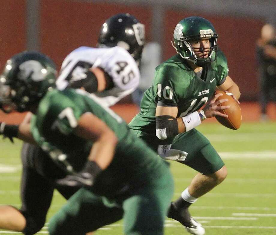 Reagan quarterback Trevor Knight is pressured by Ross Luensmann (55) of Steele in Class 5A Division II state quarterfinals action at Heroes Stadium on Saturday, Dec. 3, 2011. Photo: BILLY CALZADA, SAN ANTONIO EXPRESS-NEWS  / gcalzada@express-news.net