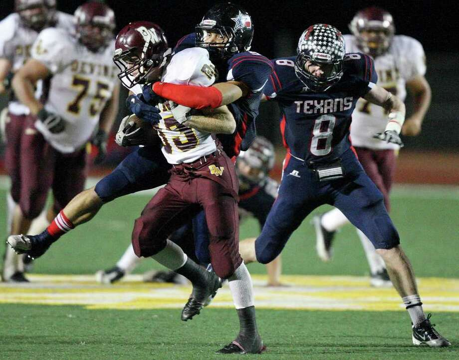 Devine's Joseph Sadler tries to shake free of Dennis Smith as Wimberley's Davis Holliman (8) closes in on the play. Photo: EDWARD A. ORNELAS, SAN ANTONIO EXPRESS-NEWS / © SAN ANTONIO EXPRESS-NEWS (NFS)
