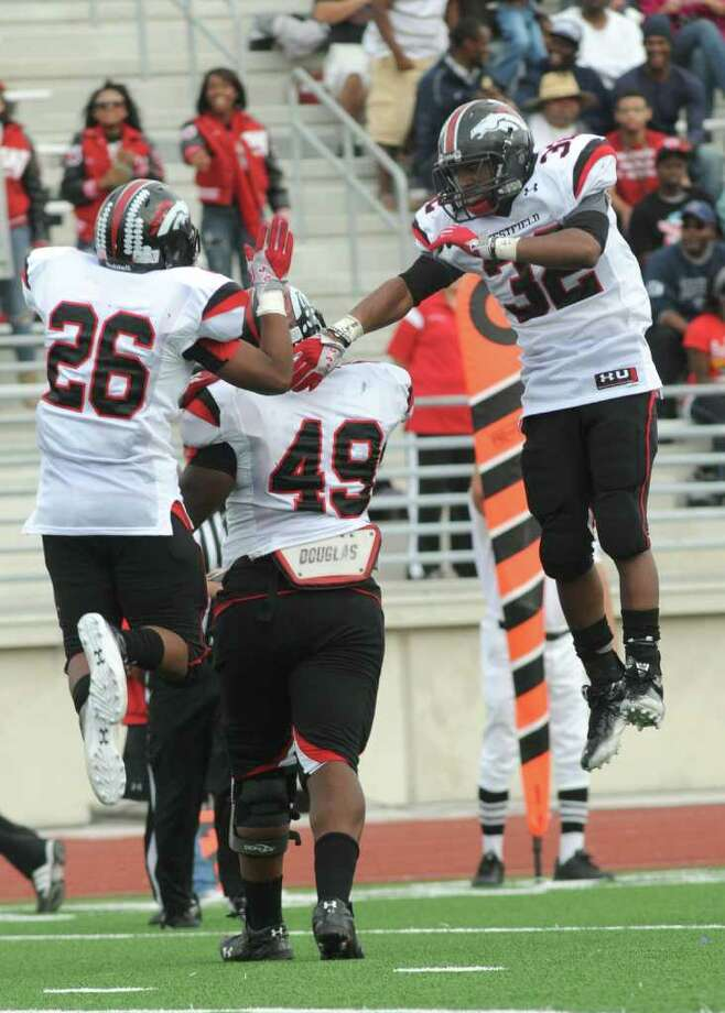Westfield senior linebackers Matt Davis, right, and Shelton Brown (#26) congratulate teammate Cliff Butler (#49), also a senior, after his fumble recovery late in the second quarter of their regional final playoff game at Turner Stadium in Humble on Saturday. Freelance photo by Jerry Baker Photo: Jerry Baker, For The Chronicle
