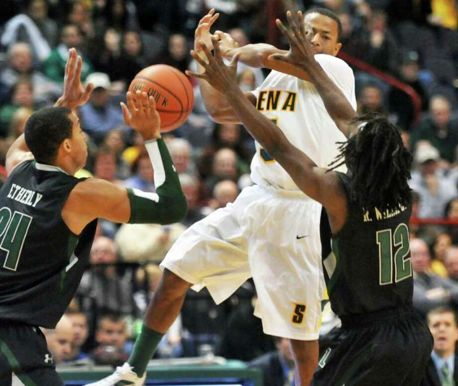 Siena's #5 Evan Hymes, center, gets tangled up with Loyola's #24 Eric Etherly,left, and  #12 R.J. Williams during the MAAC opener at the Times Union Center in Albany Saturday Dec. 3, 2011.    (John Carl D'Annibale / Times Union) Photo: John Carl D'Annibale / 00015373C