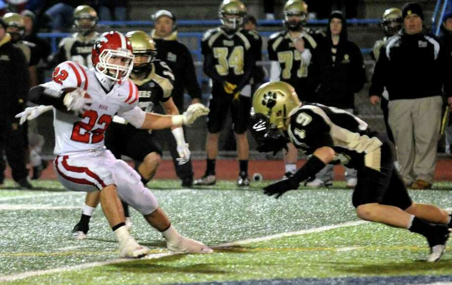 Highlights from CIAC Class L boys football semifinal action between Masuk and Daniel Hand in West Haven, Conn. on Saturday December 3, 2011.  Masuk's #22 Thomas Milone looks to dodge Hand's #19 Hunter Mayhew. Photo: Christian Abraham / www.connpost.com