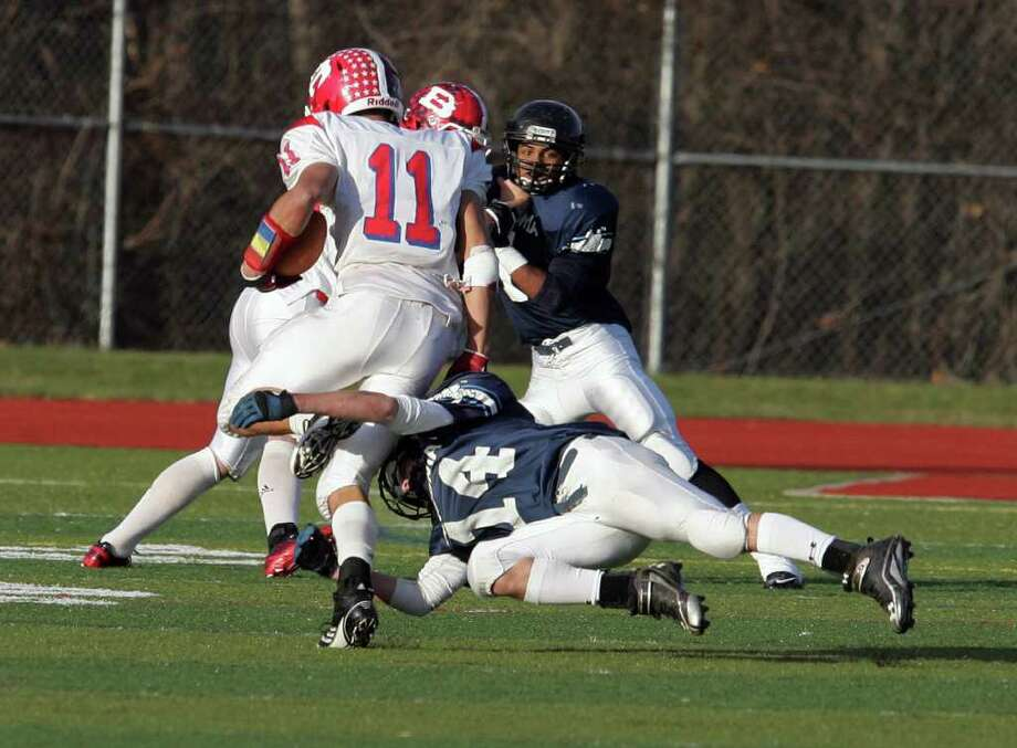 Ansonia High School's  # 14 Ryan O'Connor defends and makes the stop against Berlin High School's #11 Tom Undercuffler during  CIAC semifinal football on Saturday Nov. 3, 2011 at Sheehan HS in Wallingford, Conn. Ansonia wins the game 48-14. Photo: Mike Ross / Connecticut Post Freelance