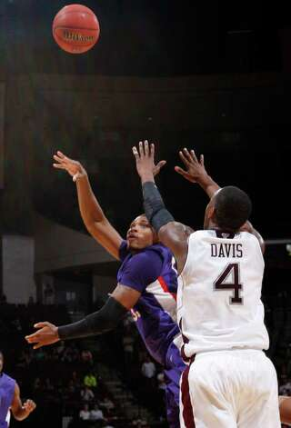 Stephen F. Austin's Jereal Scott, left, shoots the ball around Texas A&M defender Keith Davis (4) during the second half of an NCAA college basketball game on Saturday, Dec. 3, 2011, in College Station. Texas A&M won 55-42. Photo: Associated Press