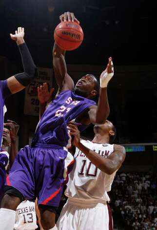 Stephen F. Austin's Jonathan King (23) rebounds the ball against Texas A&M defender David Loubeau (10) during the first half of an NCAA college basketball game on Saturday, Dec. 3, 2011, in College Station. Photo: Associated Press