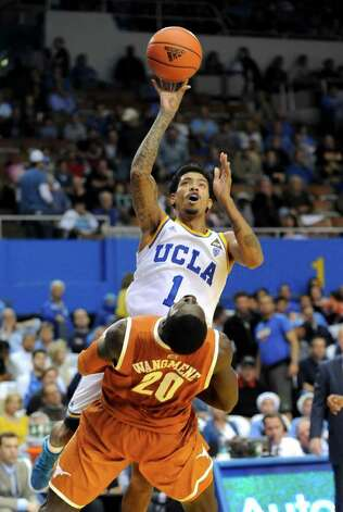 UCLA guard Tyler Lamb (1) collides with Texas forward/center Alexis Wangmene (20) as he gets a shot off during the second half of an NCAA college basketball game on Saturday, Dec. 3, 2011, in Los Angeles.  Texas won 69-59. Photo: Associated Press