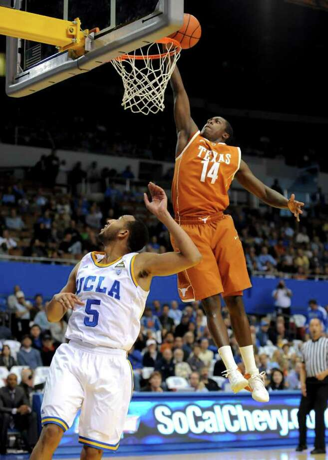 Texas guard J'Covan Brown (14) dunks the ball after getting by UCLA guard Jerime Anderson (5) during the first half of an NCAA college basketball game on Saturday, Dec. 3, 2011, in Los Angeles. Photo: Associated Press