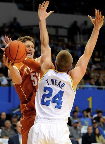 Texas forward/center Clint Chapman (53) passes around UCLA forward Travis Wear (24) during the first half of an NCAA college basketball game on Saturday, Dec. 3, 2011, in Los Angeles. Photo: Associated Press