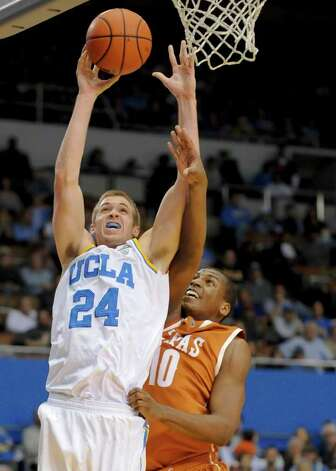 UCLA forward Travis Wear (24) gets by Texas forward Jonathan Holmes (10) for a basket during the second half of an NCAA college basketball game on Saturday, Dec. 3, 2011, in Los Angeles.  Texas won 69-59. Photo: Associated Press