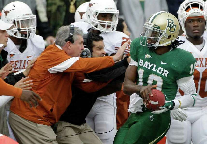 Texas head coach Mack Brown braces as Baylor quarterback Robert Griffin III (10) is forced out of bo