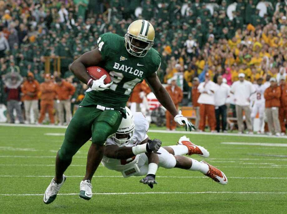 Dec. 3: Baylor 48, Texas 24. Baylor running back Terrance Ganaway (24) side steps a tackle by Texas safety Christian Scott (6) during an NCAA college football game Saturday. Photo: Tony Gutierrez, Associated Press / AP