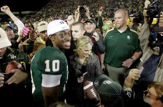 Baylor quarterback Robert Griffin III stands surrounded on the field during a post game interview following their NCAA college football game against Texas Saturday, Dec. 3, 2011, in Waco, Texas. Baylor won 48-24. (AP Photo/Tony Gutierrez) Photo: Tony Gutierrez, Associated Press / AP