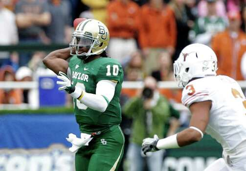 Baylor quarterback Robert Griffin III (10) passes as Texas linebacker Jordan Hicks (3) gives chase in the first half of an NCAA college football game Saturday, Dec. 3, 2011, in Waco, Texas. (AP Photo/Tony Gutierrez) Photo: Tony Gutierrez, Associated Press / AP