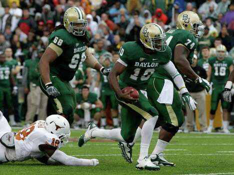 Texas 's Emmanuel Acho (18) is unabl3 to reach Baylor quarterback Robert Griffin III who runs with protection from Philip Blake (74) and Cyril Richardson (68) in the first half of an NCAA college football game Saturday, Dec. 3, 2011, in Waco, Texas. (AP Photo/Tony Gutierrez) Photo: Tony Gutierrez, Associated Press / AP