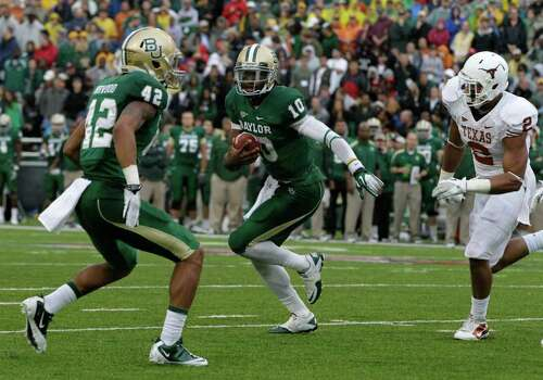 Baylor quarterback Robert Griffin III (10)finds running room as Levi Norwood (42)   helps with pressure from Texas' Keenan Robinson (2) in the first half of an NCAA college football game Saturday, Dec. 3, 2011, in Waco, Texas. (AP Photo/Tony Gutierrez) Photo: Tony Gutierrez, Associated Press / AP