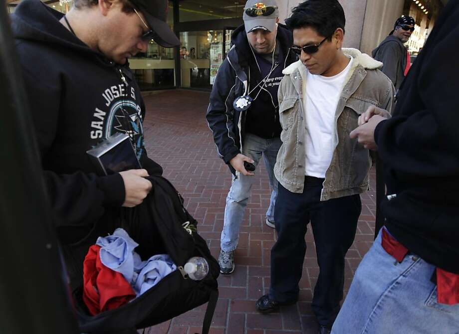 Police officers search a backpack after they arrest a man (right) for allegedly buying known stolen perfume from an undercover officer near Powell and Market streets in San Francisco, Calif. on Wednesday, Nov. 30, 2011. Police officers conducted a reverse-sting to arrest people who purchase stolen goods, including perfume and cell phones. Photo: Paul Chinn, The Chronicle