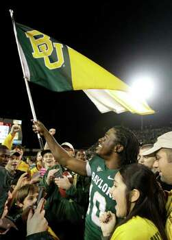 Baylor quarterback Robert Griffin III (10) waves a university flag as he walks off the field surrounded by fans following their NCAA college football game against Texas, Saturday, Dec. 3, 2011, in Waco, Texas. Baylor won 48-24. Photo: AP