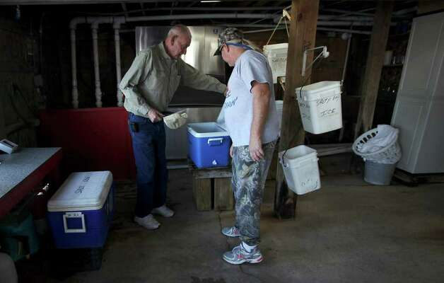 Salty Dogs Bait Shop owner Ron Coble, left, and employee Mark Hartsell check out ice-packed mullet in Rockport, Texas, Tuesday, Nov. 29, 2011. According to shop owner Ron Coble, the baitfish died due to the Red Tide in the area. The Aransas Project is suing officials with the Texas Commission on Environmental Quality for what they content is a failure to control the flow of fresh water from the rivers that empty into the refuges that contributed to the death of whooping cranes between 2008-2009. With the ongoing drought and low river water flow, high salinity in the waters of the bay caused a bloom of red tide that lead to the closing of the oyster season and the decline in blue crabs. The crabs are the main source of food for the cranes. Photo: JERRY LARA, Jerry Lara/glara@express-news.net / SAN ANTONIO EXPRESS-NEWS